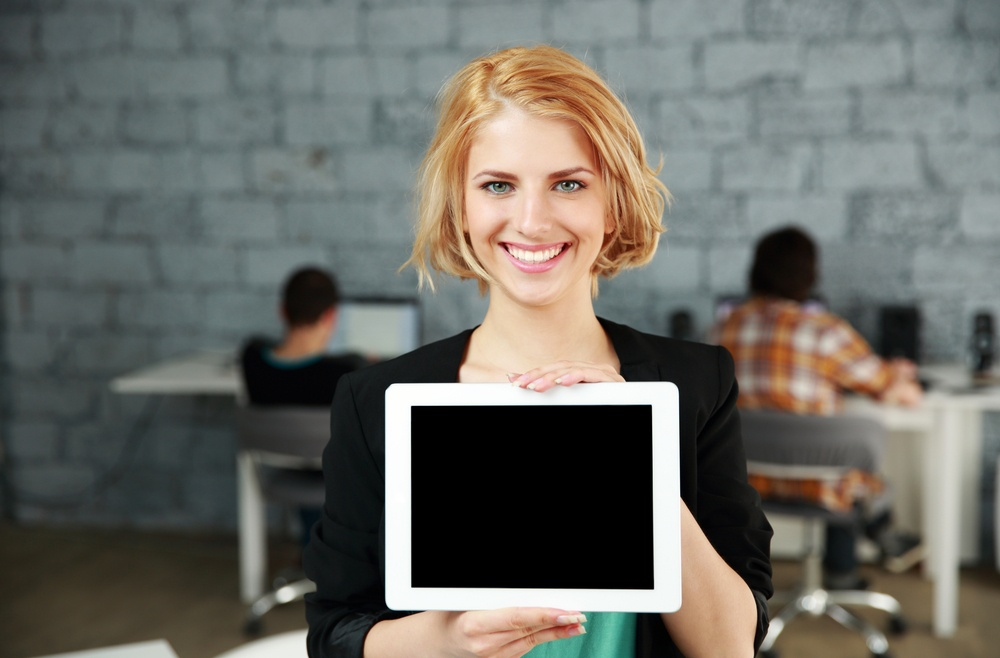 Young happy woman showing blank tablet computer screen in office.jpeg