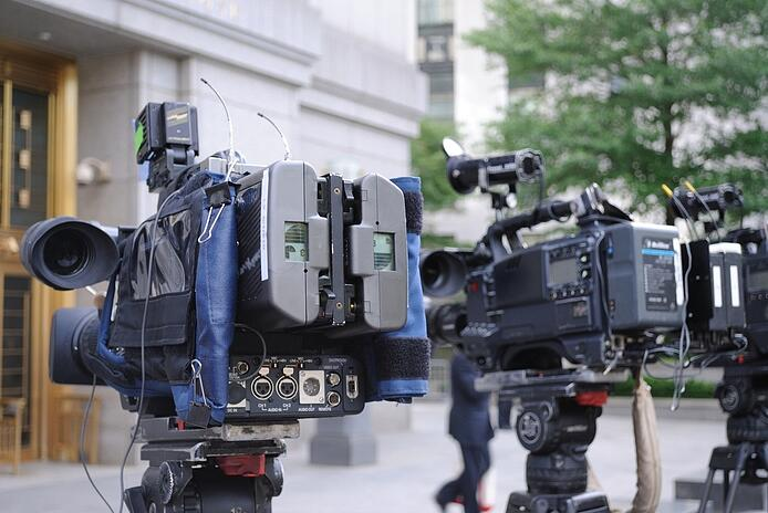 video cameras poised outside of a courthouse.jpeg