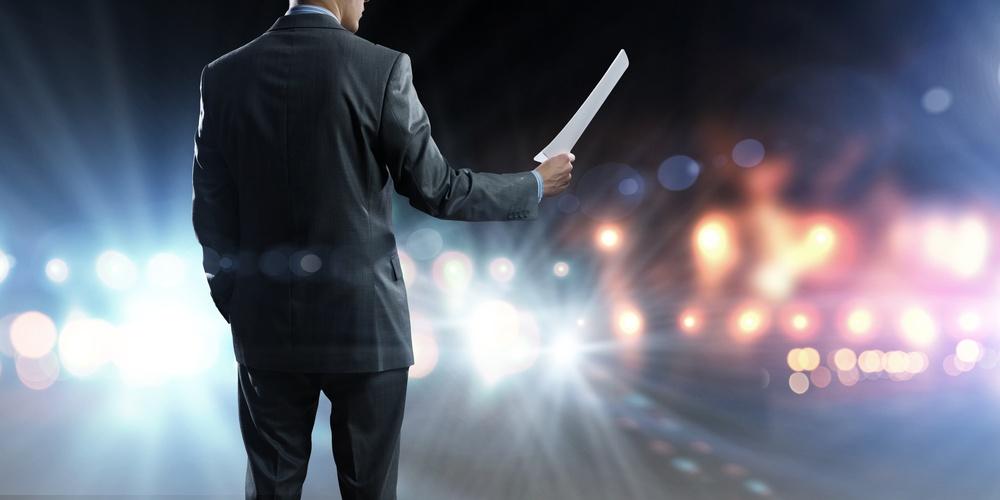 Back view of businessman speaker standing on podium in lights.jpeg