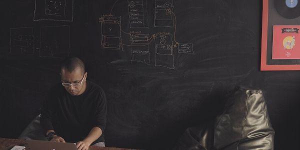 man-working-on-a-laptop-in-front-of-a-blackboard